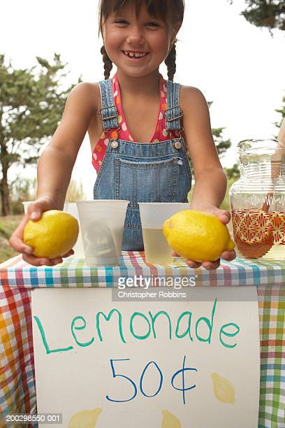 Girl (5-7) tending lemonade stall, holding lemons, smiling, portrait