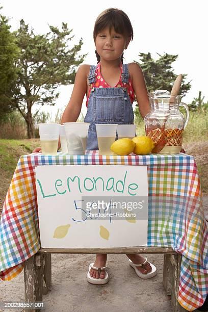 Girl (5-7) tending lemonade stall, portrait, low angle view