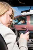 A teenager texting on her phone and looking away from the road where she is about to hit a truck with a woman in the drivers seat.