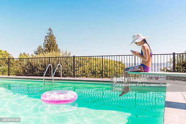 Girl texting on mobile phone by pool