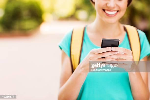Mädchen SMS auf Smartphone am Campus der Universität