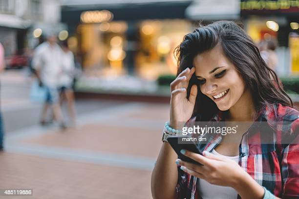 Girl texting on smartphone outside