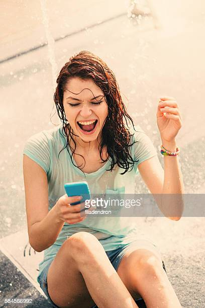 Girl texting under a fountain