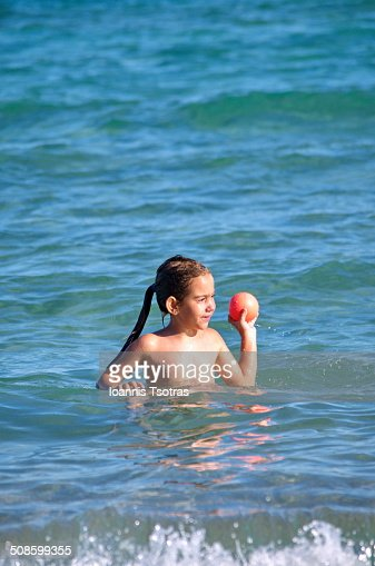 Girl throwing a ball in the sea : Stock Photo