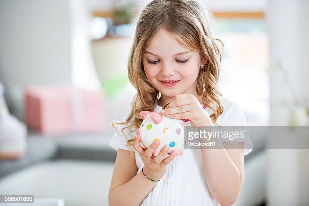 Girl throwing coin into piggy bank