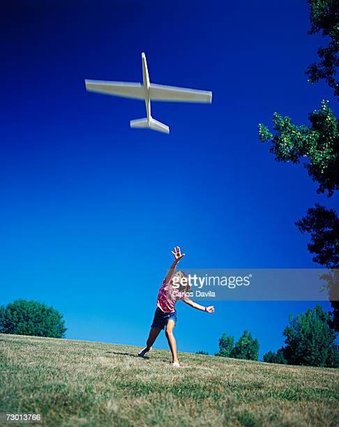 Girl (10-11) throwing model aeroplane in air