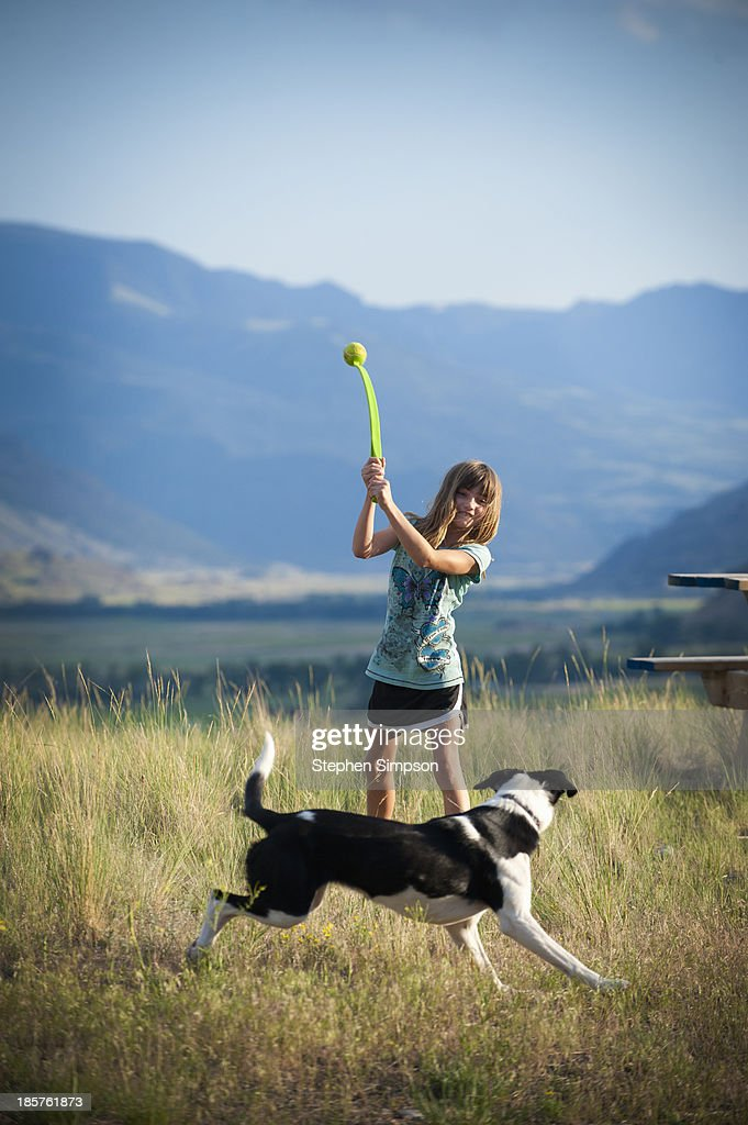 girl throwing tennis ball for dog to chase : Stock Photo