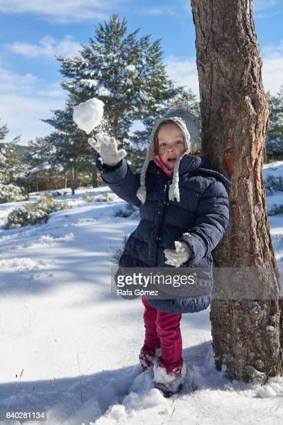 Girl throws a snowball to the camera