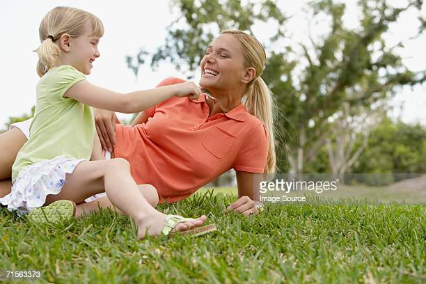 Girl tickling mother with feather
