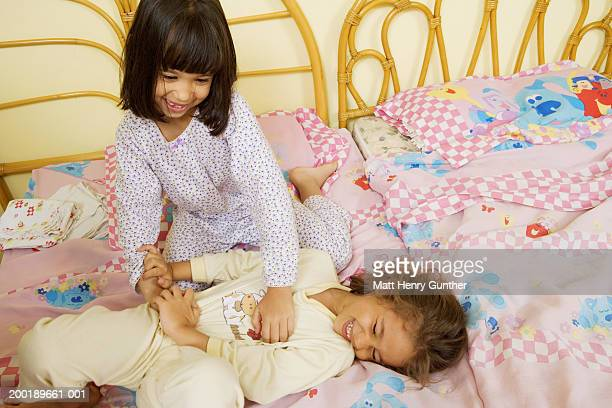 Girl (4-6) tickling sister (3-5) in bed, elevated view