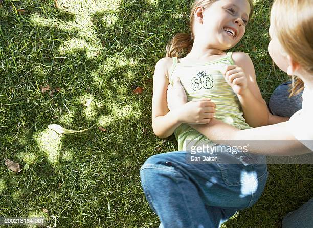 Girl (7-9) tickling younger girl (5-7) lying on grass, close-up
