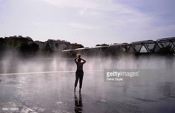 A girl ties her hain while cooling down in a fountain in the Madrid Rio playground on September 5 2016 in Madrid Spain A threeday heatwave has hit...