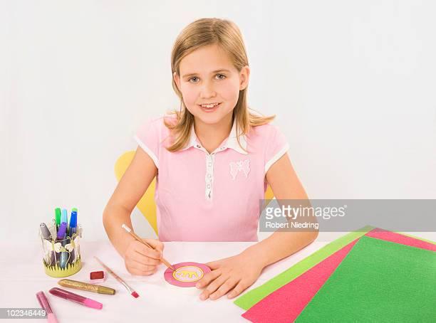 Girl (8-9) tinkering, smiling, portrait
