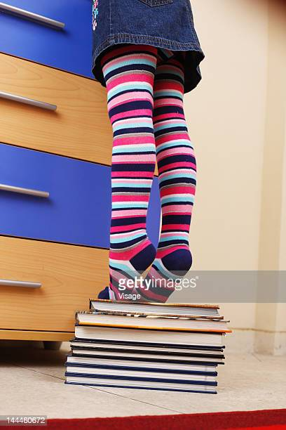 Girl tiptoeing on a stack of books