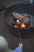 Girl toasting a marshmallow over campfire