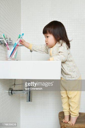 Girl toddler on tiptoe reaching over bathroom sink