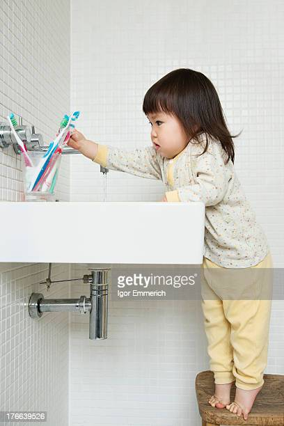 Girl toddler on tiptoe reaching over bathroom sink