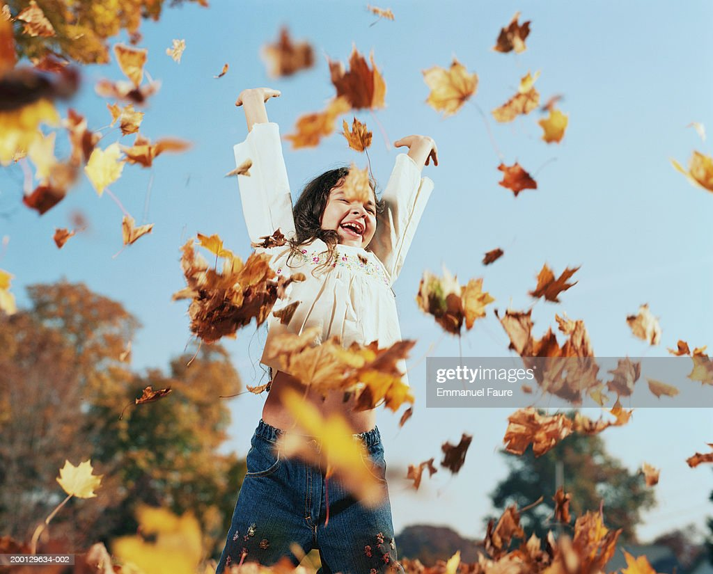 Girl (8-10) tossing leaves in air, autumn, low angle view : Stock Photo