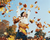 Girl (8-10) tossing leaves in air, autumn, low angle view