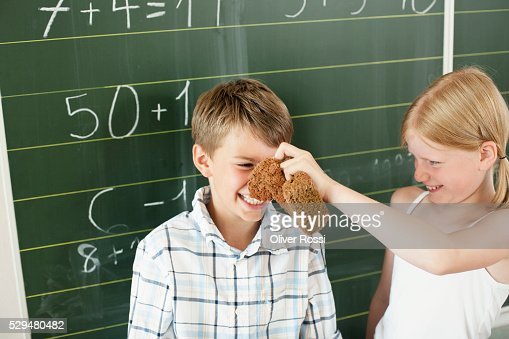 Girl touching boy with eraser : Stock Photo