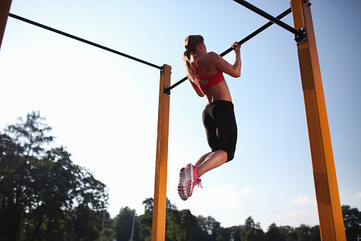 Girl training on chin-up bar outdoor