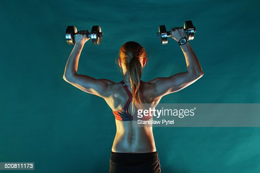 Girl training with dumbbells, back view, green ba : Stock Photo