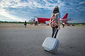 Girl traveler with luggage going to plane for travel