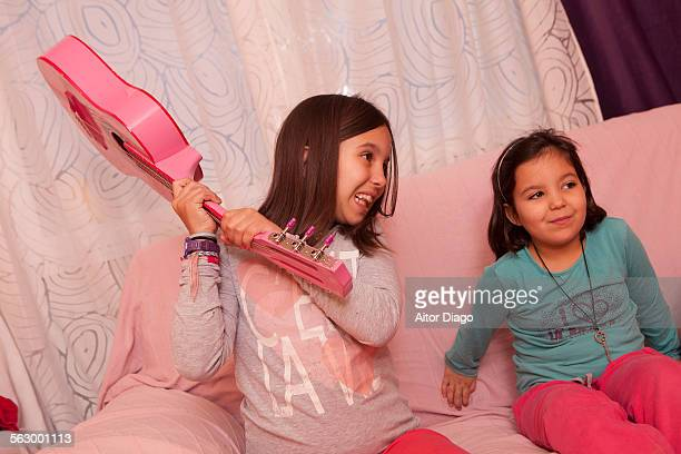 Girl trheats little sister with a rosa guitar