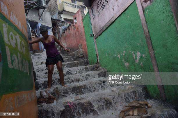 TOPSHOT A girl tries to clean stairs in the Jalousie neighborhood of PortauPrince after heavy rains on August 22 2017 / AFP PHOTO / HECTOR RETAMAL