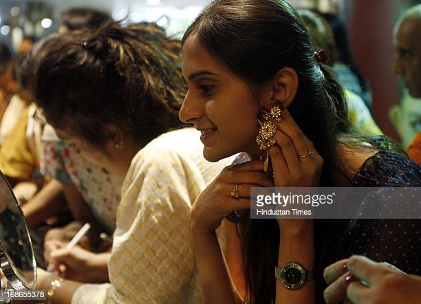 A girl trying the gold ear pieces in a Jewellery shop at Janpath on the occasion of Akshaya Tritiya on May 13 2013 in New Delhi India Akshaya Tritiya...