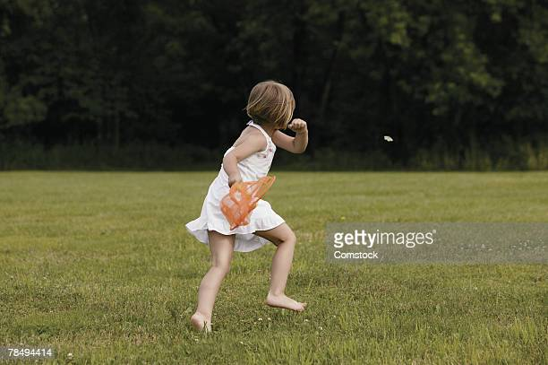 Girl trying to catch butterfly with net