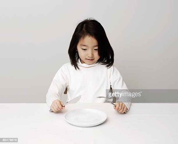 Girl trying to eat meal toward empty plate
