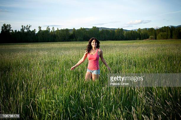A girl twirls through tall grass on a sunny day in Idaho.