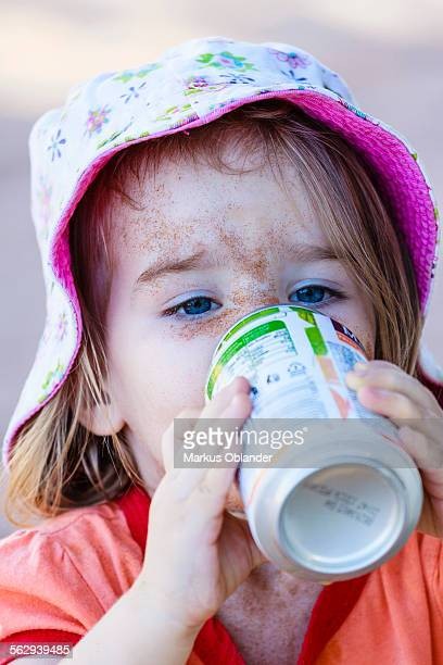 Girl, two years, face caked in sand, drinking from beverage can, Namibia