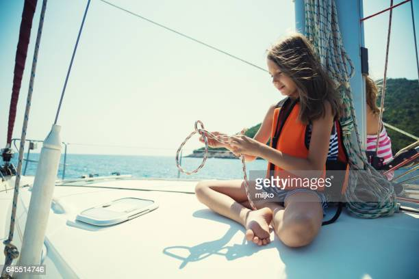 Girl tying knots on vacation on sailboat