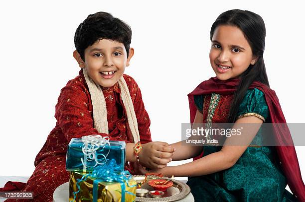 Girl tying rakhi on her brother wrist