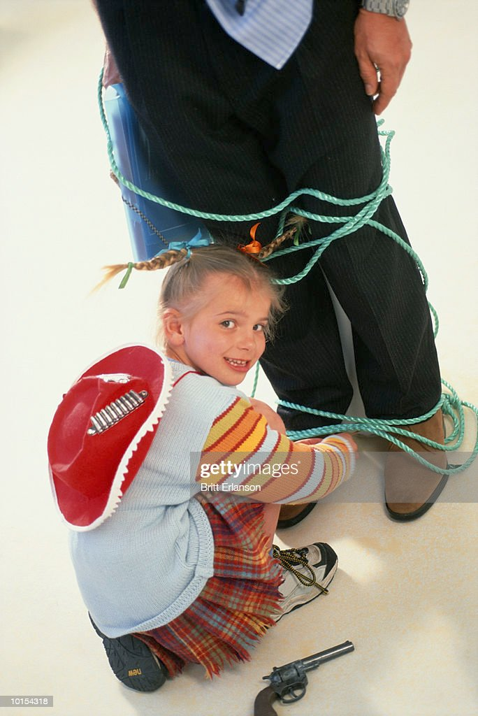 Girl (6-8) tying rope around father at home, elevated view : Stock Photo