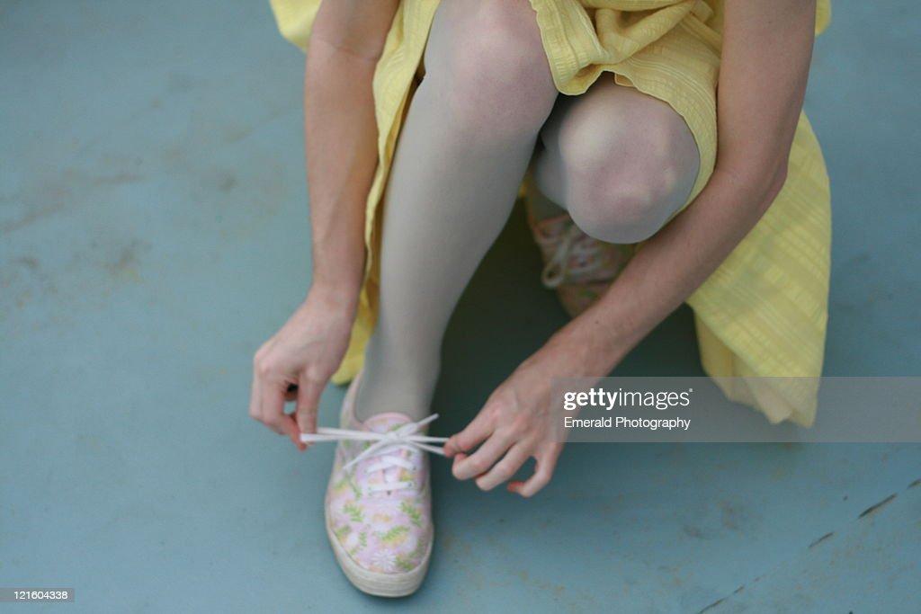 Girl tying shoe laces : Stock Photo