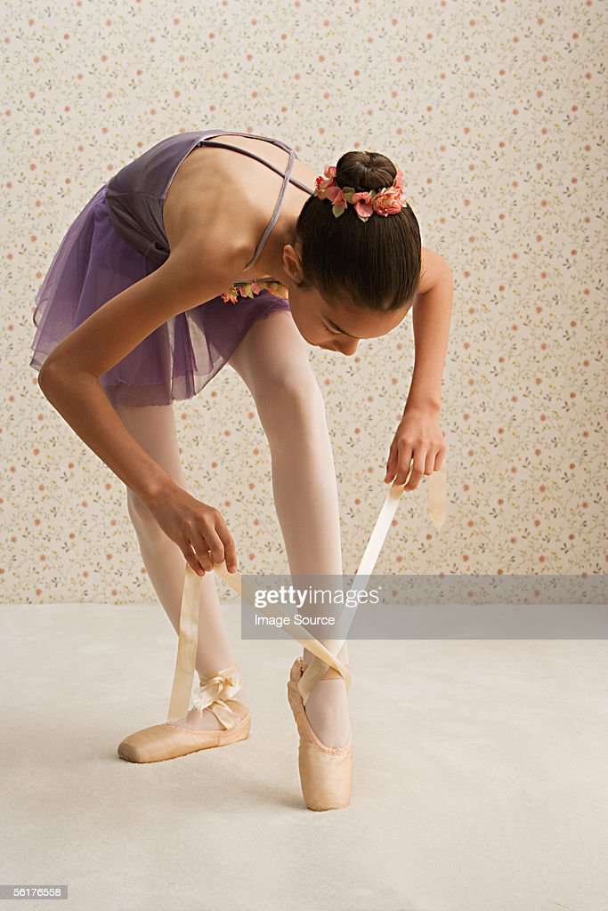Girl tying the ribbons on her ballet slippers
