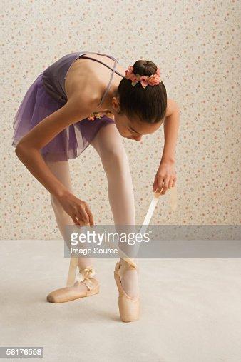 Girl tying the ribbons on her ballet slippers