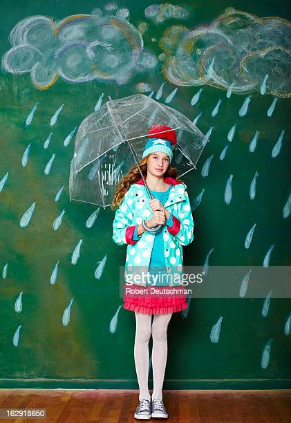 A girl under an umbrella in the rain.