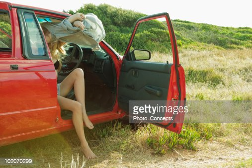 Girl undressing in car : Stock Photo