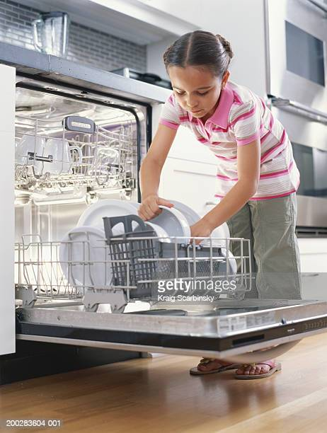 Girl (6-8) unloading dishwasher, low angle view