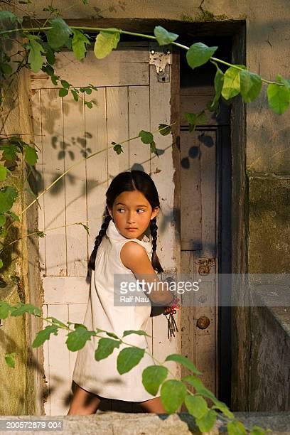 Girl (5-7) unlocking garden door