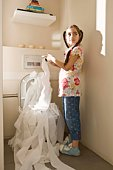 Girl unrolling toilet paper into toilet