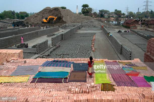 Girl uses a pile of brick as clothesline for her family working in the brick kiln at Kamduni Kamduni West BengalIndia 080317 The brick kilns of...