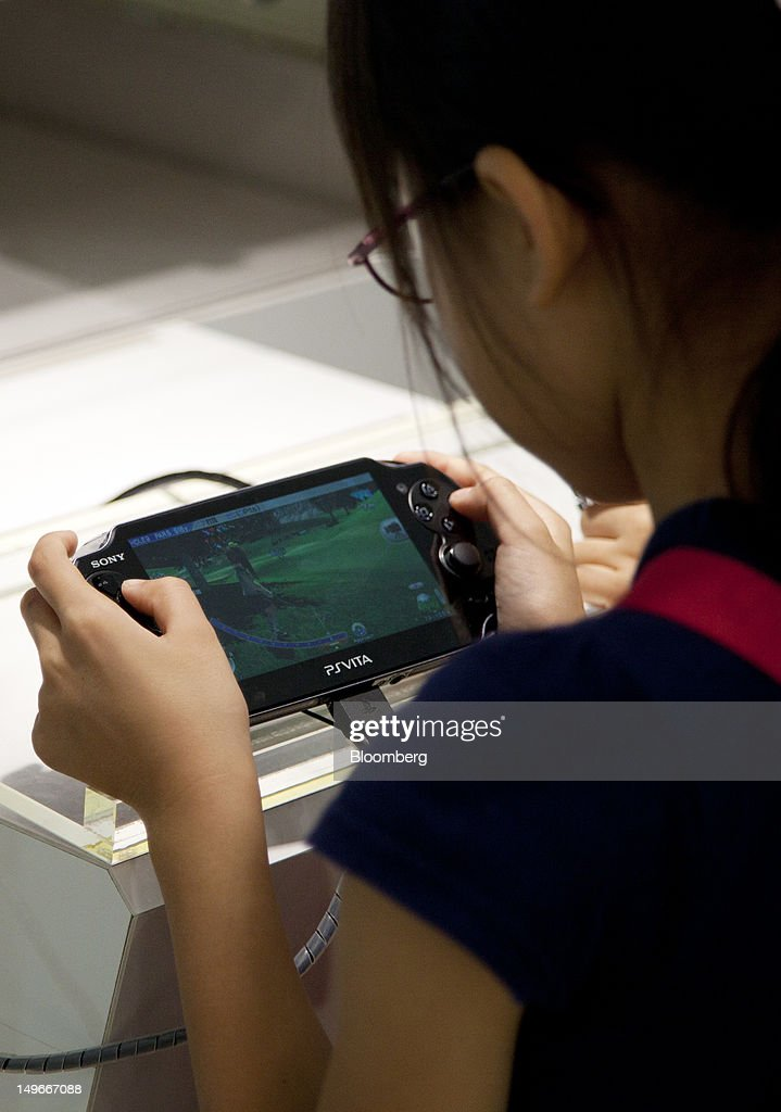 A girl uses a Sony Computer Entertainment Inc.'s PlayStation Vita (PS Vita) at the company's showroom in Tokyo, Japan, on Thursday, Aug. 2, 2012. Sony Corp., reeling from four consecutive annual losses, cut its full-year profit forecast as Japan's biggest exporter of consumer electronics suffers from slowing demand while the yen's gain erodes overseas earnings. Photographer: Tomohiro Ohsumi/Bloomberg via Getty Images