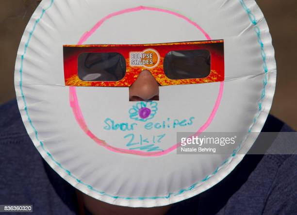 A girl uses bespoke eclipse glasses to watch the eclipse on Menan Butte August 21 2017 in Menan Idaho Millions of people have flocked to areas of the...