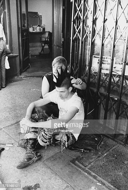 A girl uses hairspray to style a punk's mohawk haircut on St Mark's Place New York City circa 1979