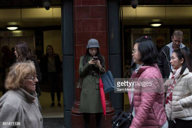 A girl uses her mobile phone outside Covent Garden Underground Station on 19th December 2016 in London United Kingdom From the series Our Small World...